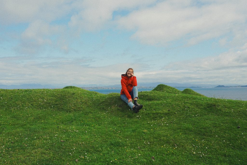 A woman sitting in a grassy field at Brothers Point, Isle of Skye
