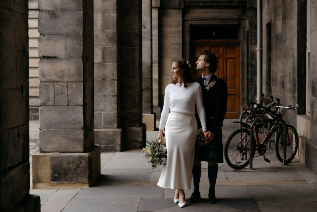 A bride and groom standing in an archway.