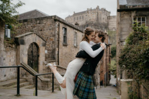 A bride, ArcticSabrina, and a groom hugging in the foreground. The bride has one heel in the air and the two are embracing. Edinburgh Castle in the background