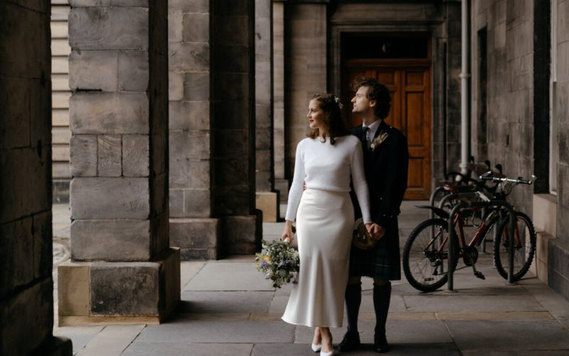 A bride and groom at Edinburgh City Chambers, outside the entrance posing under an archway