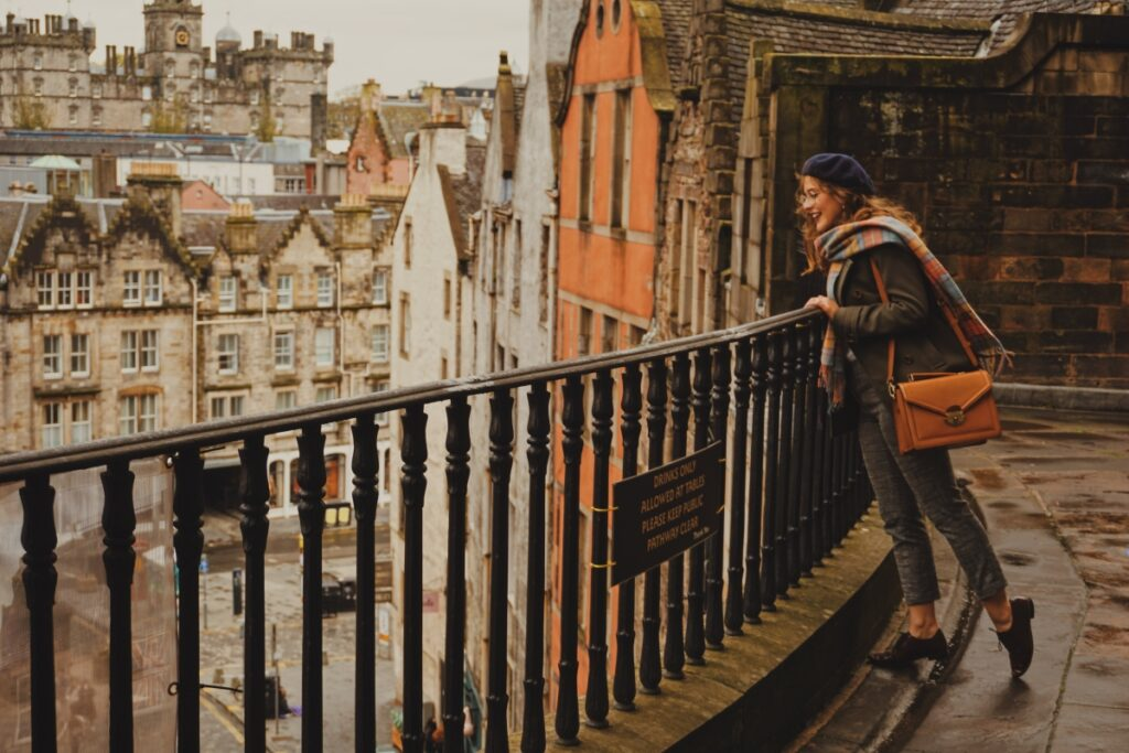 A girl looks over a fence at the side of a terraced street, looking at the street below. In the middleground are buildings of grey stone, orange and white plaster. In the background is George Heriots School, a large stone building in the 1600s.