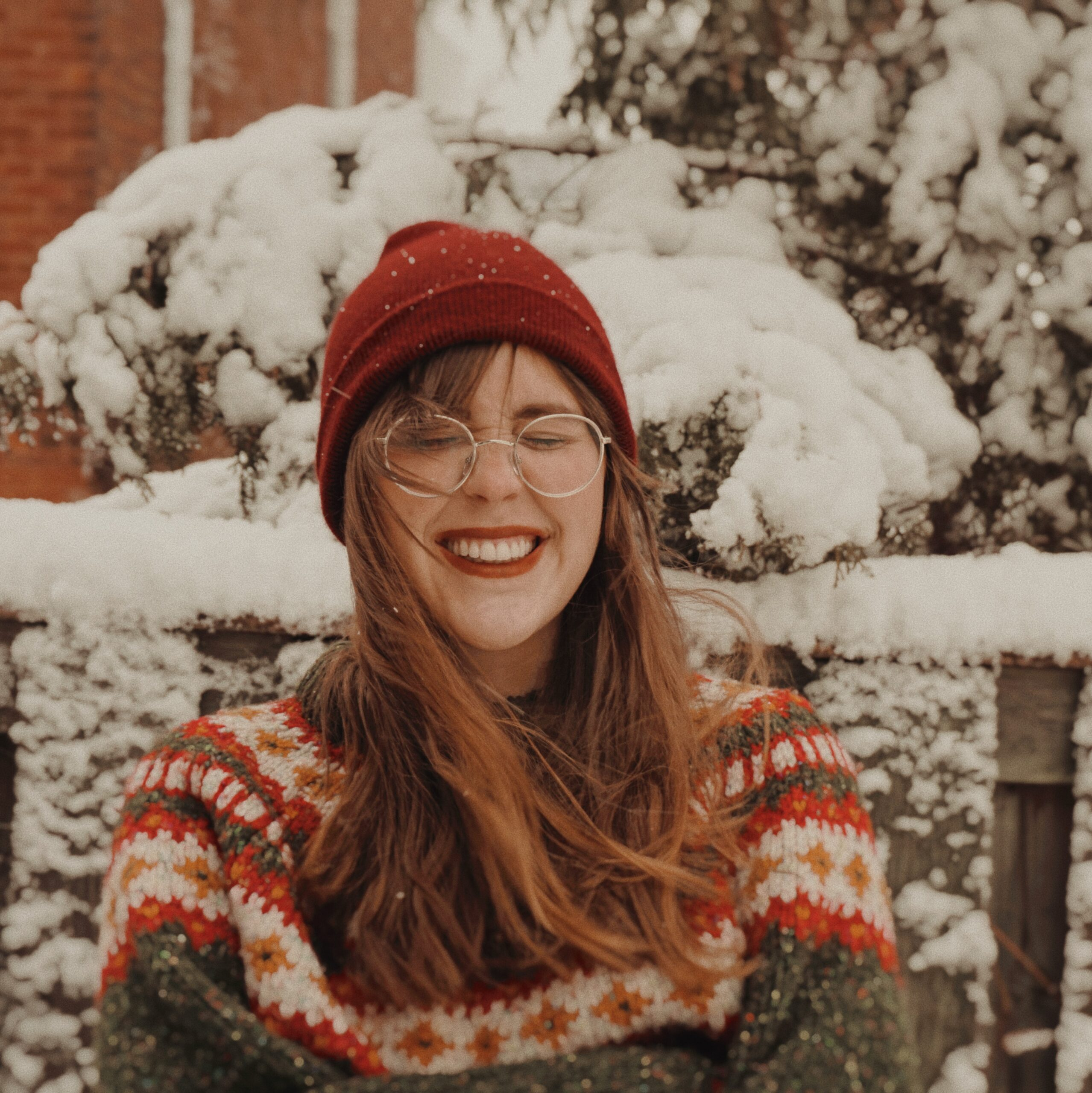 A smiling girl wears a red beanie hat and nordic style knit jumper in front of a snowy fence.