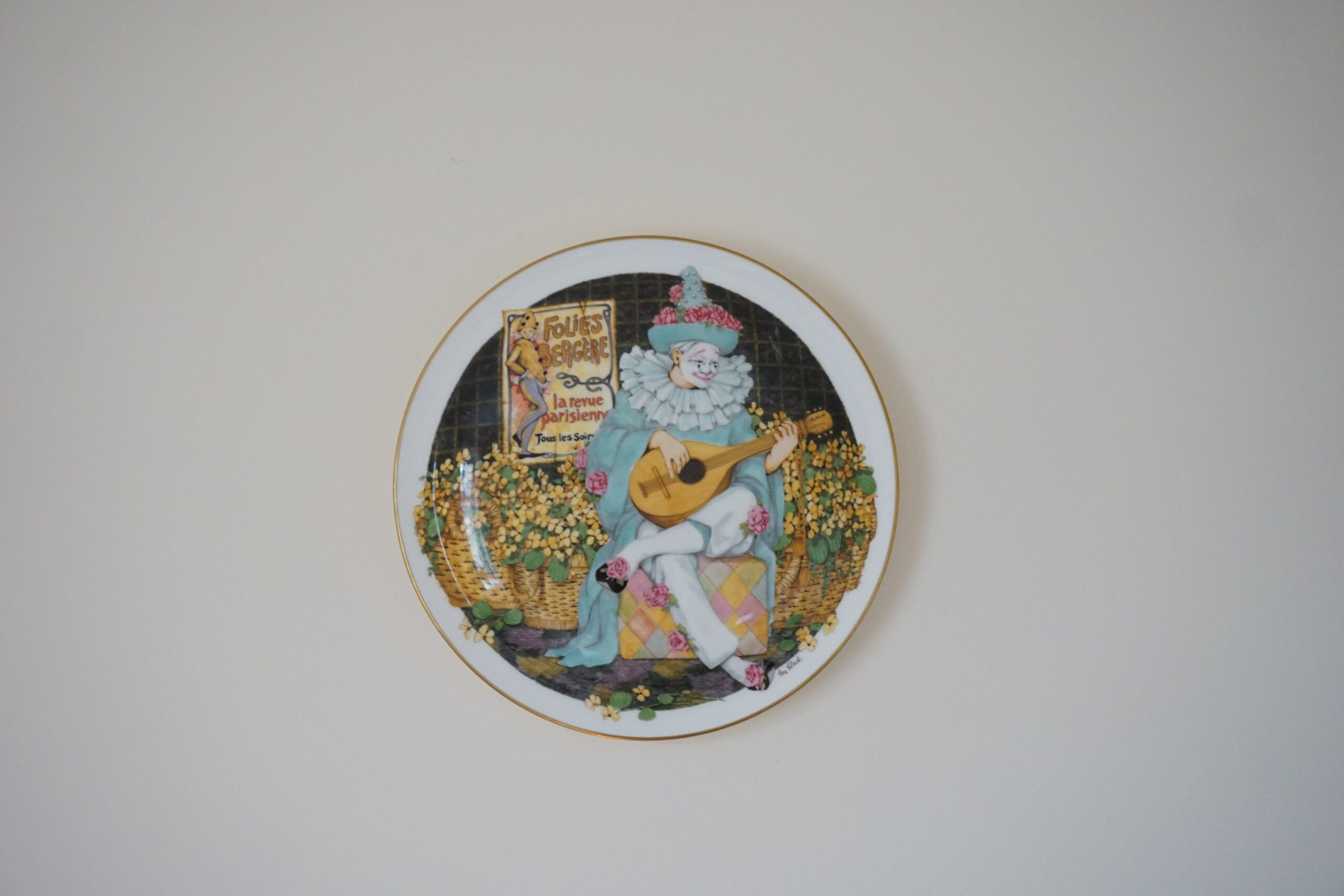 a ceramic plate painted with a mime on the front, hanging on a beige wall