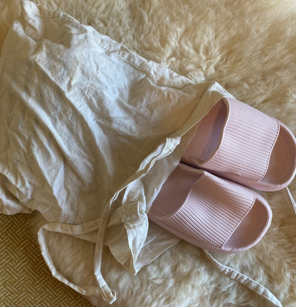 A pair of pink slide shoes sticking out of the top of a beige tote bag, laying on top of a sheepskin rug.