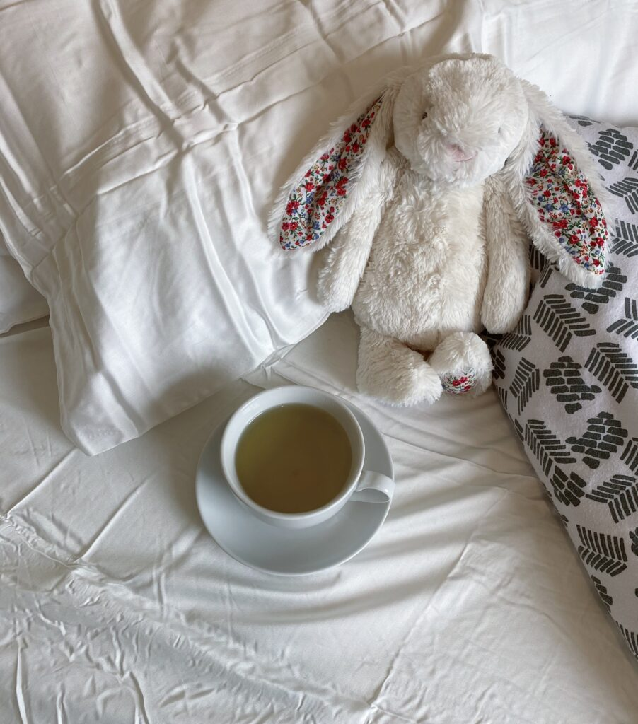 A pillow lays on a bed with white, silky sheets, it props up a white toy bunny, sitting next to the bunny is a cup of green tea.